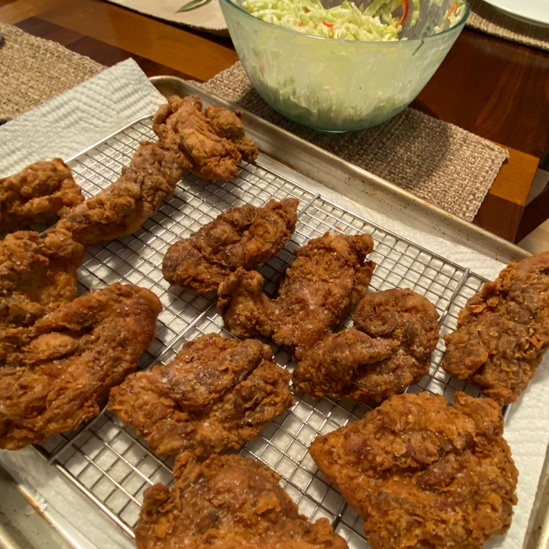 fried chicken on a baking sheet with slaw to the side (slaw has ripe red Santa Fe pepper slices).