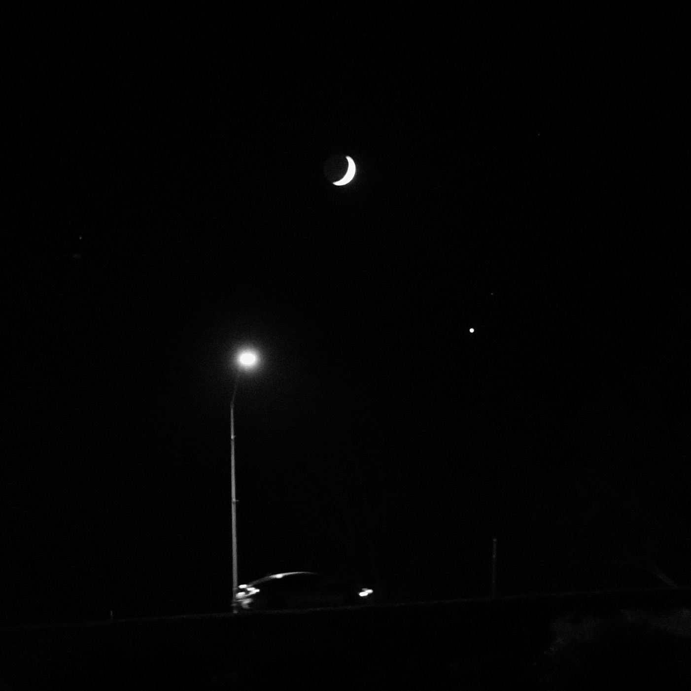 waxing crescent moon, venus, street light, and a car driving up a bridge. black and white photo.