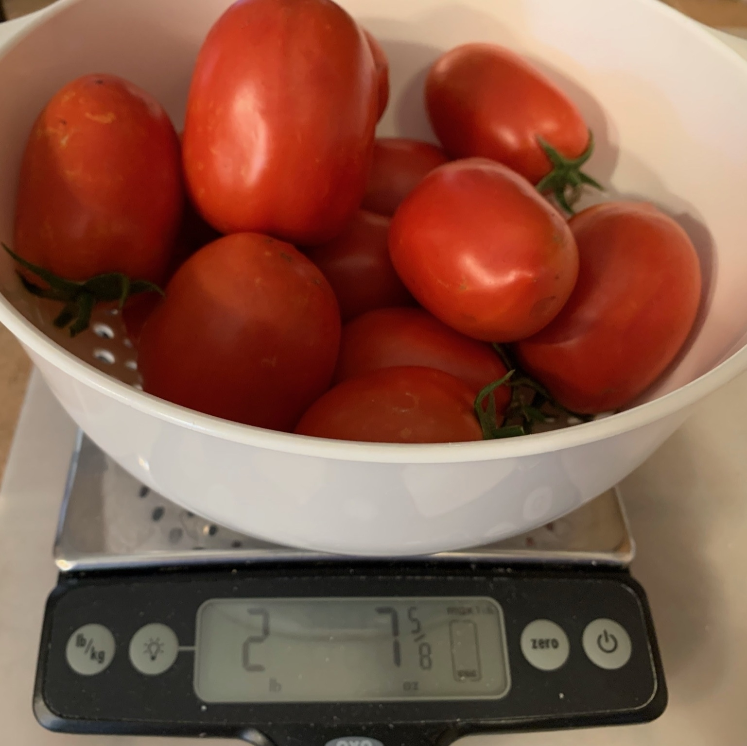 tomatoes sitting on a scale reading about 2 pounds