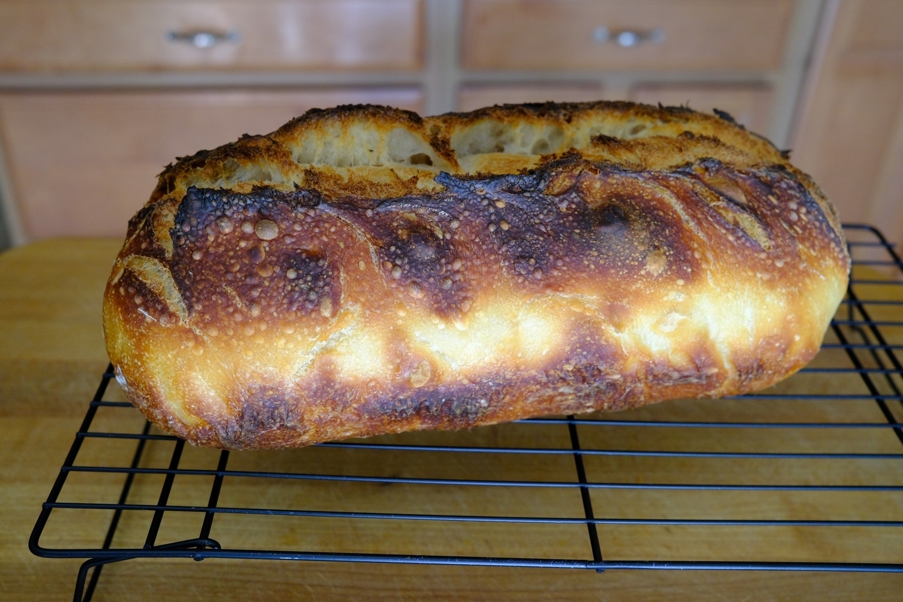 well caramelized sourdough loaf on a rack.